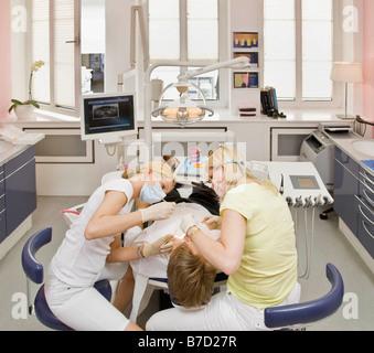 Zahnärztin, arbeitet an einem männlichen Patienten - Stockfoto