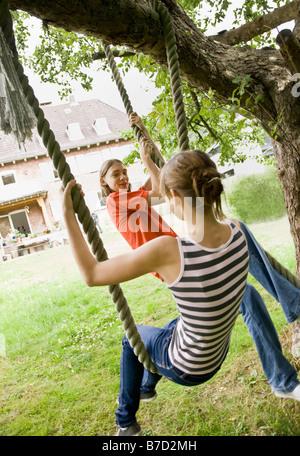 Junge Mädchen und Jungen auf einem Baum schwingen - Stockfoto