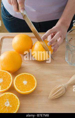 Frau schneiden Orangen - Stockfoto