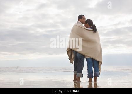 Paar in der Decke am Meer - Stockfoto