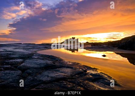 Sonnenaufgang über den Strand und Burg von Bamburgh an der Northumberland Küste - Stockfoto
