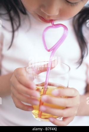 Mädchen trinken Saft mit Stroh - Stockfoto