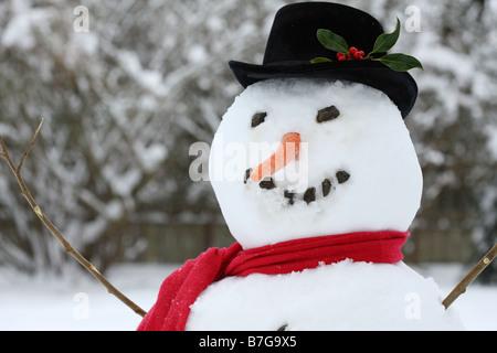 Nahaufnahme von einem Schneemann mit Mütze, Schal und Karotte Nase - Stockfoto