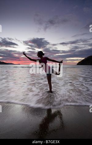 Junge Frau tut Yoga in der Brandung am Strand bei Sonnenuntergang in Playas del Coco, Guanacaste, Costa Rica. - Stockfoto