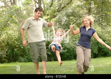 Junges Paar swingenden Kind während des Gehens, Regina, Saskatchewan - Stockfoto