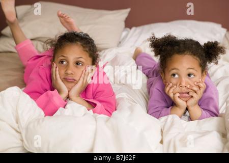 Mulatte Schwestern im Bett. 3 und 6 Jahre alt. - Stockfoto