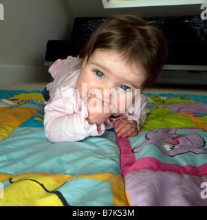 Ein sechs Monate altes Babymädchen kaut auf ihrer Hand, während versuchend, zu kriechen. - Stockfoto