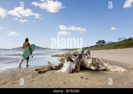 Surfer zu Fuß auf der Küste von Playa Grande in Costa Rica. - Stockfoto