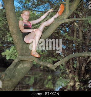 Mädchen in einem Baum über einen Fluss thront - Stockfoto