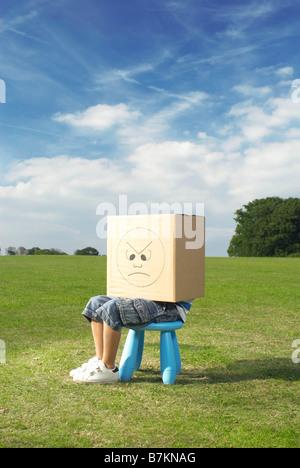 Junge auf Hocker mit Box auf Kopf - Stockfoto