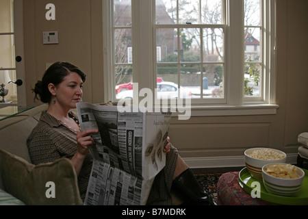 Eine Frau sitzt in ihrem Wohnzimmer, Zeitung zu lesen. - Stockfoto