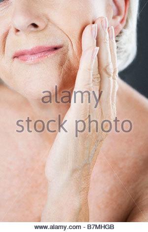 Eine ältere Frau ihre Wange berühren - Stockfoto