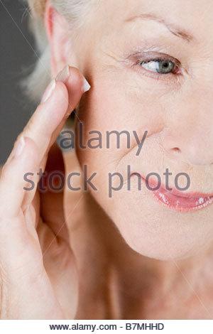 Eine ältere Frau anwenden Feuchtigkeitscreme auf ihr Gesicht - Stockfoto