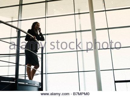 Eine Geschäftsfrau, die auf einem Mobiltelefon in einem modernen Bürogebäude im Gespräch - Stockfoto
