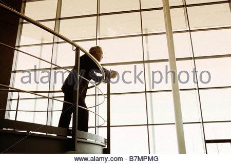 Ein Geschäftsmann mit Blick auf Balkongeländer in ein modernes Bürogebäude - Stockfoto