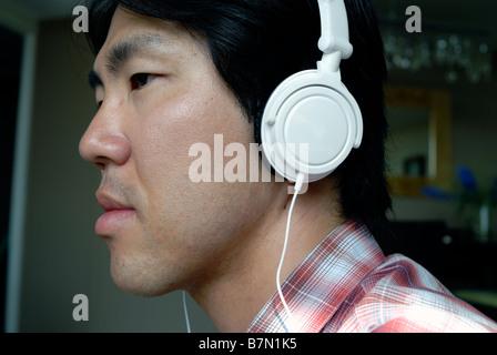 """""""Asiatische Jüngling"""" Portrait anhören von Musik über Kopfhörer """"MP3-Musik-Player"""" """"I Pod"""" Portrait Silhouette Kopf - Stockfoto"""