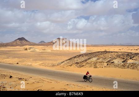 weibliche touring Radfahrer in weite offene Landschaft der westlichen Wüste Ägyptens - Stockfoto