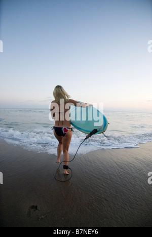 Eine blonde junge weibliche Surfer mit einem Surfbrett am Strand bei Sonnenuntergang. Malibu, Kalifornien, USA. - Stockfoto