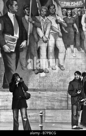 Zwei Touristen vor ein Wandbild für den Ruhm des Sozialismus auf dem Reich-Luft-Ministerium Gebäude, Deutschland. - Stockfoto
