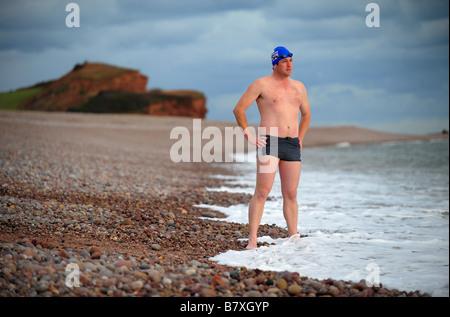 Ein Mann bereitet sich auf das Tragen einer Badekappe schwimmen gehen und am Strand von Budleigh Salterton Schutzbrillen. - Stockfoto