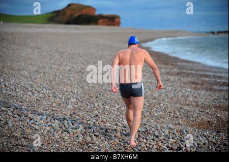 Ein Mann zu Fuß in Richtung Meer, schwimmen zu gehen, das Tragen einer Badekappe und Brille am Strand von Budleigh - Stockfoto