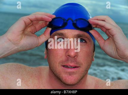 Ein Mann bereitet sich auf Meer schwimmen eine Badekappe tragen gehen und am Strand von Budleigh Salterton Schutzbrillen. - Stockfoto