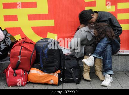Ein junges Paar, suchen sehr müde, sitzt mit Gepäck auf eine kleine Mauer im Bahnhof Nanchang, Jiangxi, China. 5. - Stockfoto