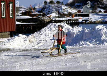 Norwegen, Lofoten-Inseln. Kind auf Sparkstotting kick Schlitten. Eine traditionelle Transportmittel in Schnee und - Stockfoto