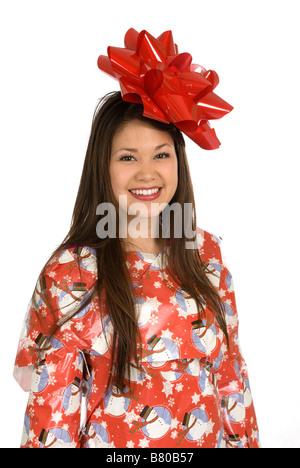Eine junge asiatische Frau lächelt, als sie in Weihnachts-Geschenkpapier eingewickelt ist und garniert mit einer - Stockfoto