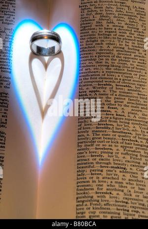 Nahaufnahme von einer herzförmigen Schatten vom Licht fällt auf einen Ehering neben Worte über die Liebe in einem - Stockfoto