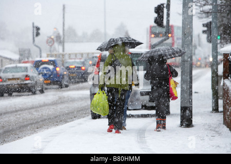Frauen gehen auf Schnee bedeckt Wanderweg vorbei an Warteschlange des Verkehrs im Schneesturm Einkaufstaschen tragen - Stockfoto