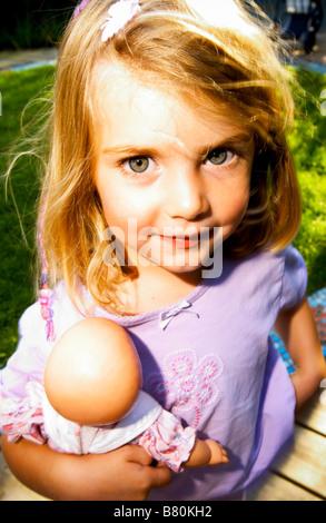 kleines Mädchen hält Babydoll glücklich
