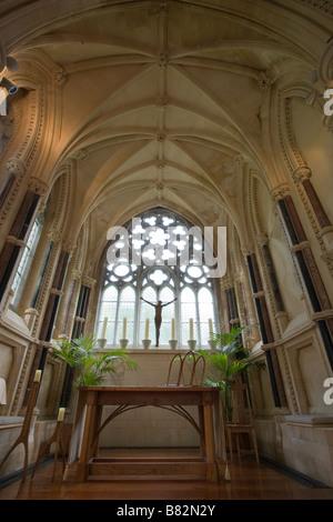 Christus und Altar. Eine Skulptur des gekreuzigten Christus umrahmt von großen Kerzen gegen das Fenster der Miniatur - Stockfoto