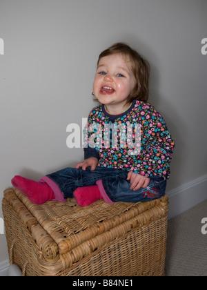 Ein einjähriges Baby Spaß sitzen auf einem Weidenkorb Spielzeug - Stockfoto