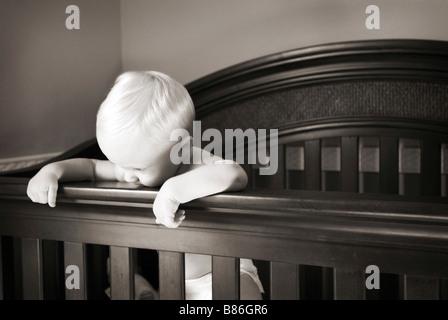 Baby in der Krippe stehen - Stockfoto