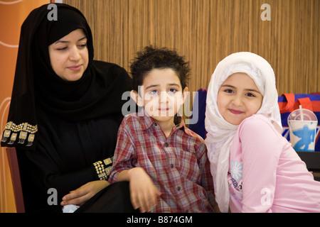 Muslimische Mutter und Kinder in der Abflughalle des Bahrain international Airport. - Stockfoto