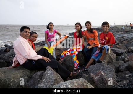 Familie auf Felsiger Strand in der Nähe von Hazira, Surat, Gujarat. Indien. Es gibt Gas / Öl-rig im Hintergrund. - Stockfoto