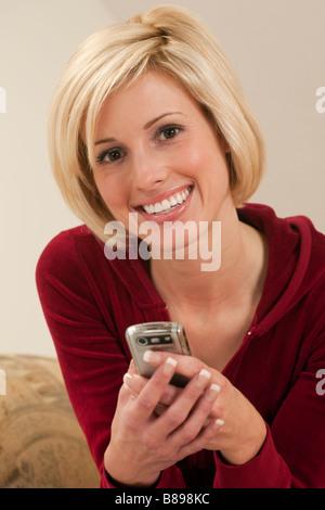 Schöne Frau von SMS-Nachrichten auf ihrem Handy - Stockfoto