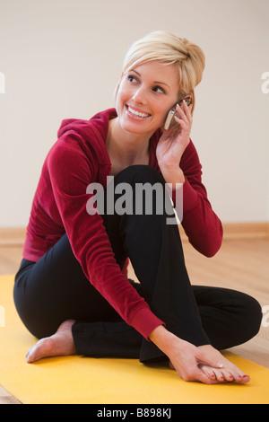 Schöne Frau auf ihrem Handy sprechen und sitzt auf einer Gymnastikmatte - Stockfoto