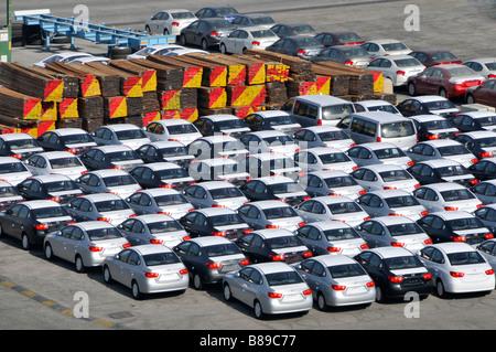 Bahrain blickte hautnah Dockside Lagerung von importierten Neuwagen und große Haufen von Holz wartet auf Verteilung - Stockfoto