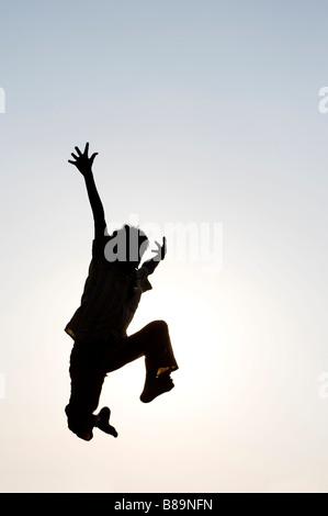 Silhouette Profil eines jungen indischen Hintergrund Sonne Einstellung springen. Indien - Stockfoto