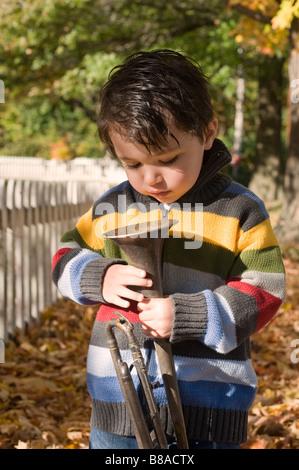 Drei Jahre alter Junge spielt mit seiner Trompete außerhalb an einem Herbsttag - Stockfoto