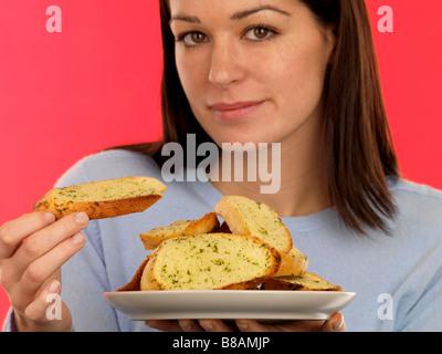 Junge Frau das Essen frisch zubereiteten italienischen Stil Knoblauchbrot auf rotem Hintergrund mit Ihren Fingern - Stockfoto