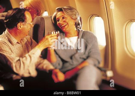 FL4788, BSE-Studio; Älteres paar Weingläser Flugzeug Toasten - Stockfoto