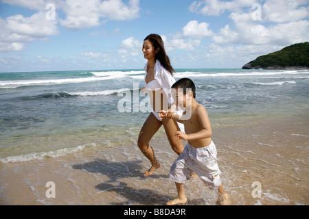 Mutter und Sohn laufen und spielen am Strand, Amerika - Stockfoto