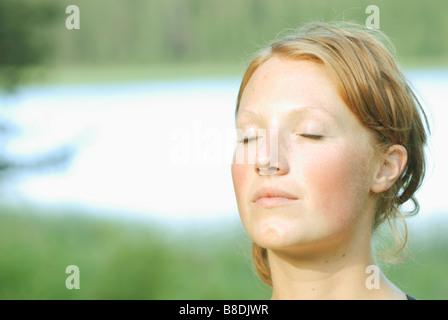 Weibliches Gesicht mit Augen geschlossen, Äsche See, Riding Mountain National Park, Manitoba, Kanada - Stockfoto