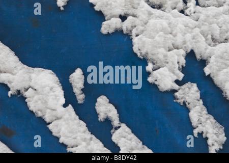 Blaue Metallplatte mit Schnee bedeckt. - Stockfoto