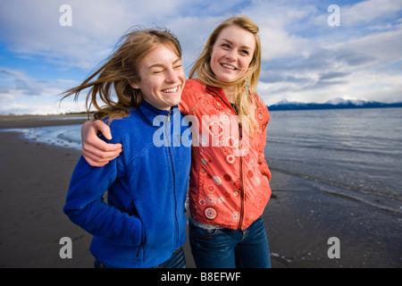 Zwei junge Frauen gehen Arm in Arm am Strand des Bischofs in Homer, Alaska - Stockfoto
