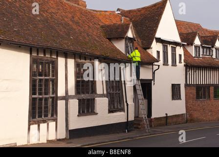 Fensterputzer am Arbeitsplatz auf eine Leiter trägt einen hohe Sichtbarkeit Mantel in Lavenham, Suffolk, Uk - Stockfoto