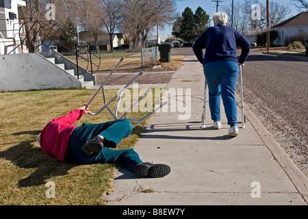 Zwei ältere Senioren gehen weg mit Wanderern, die Frau stolperte des Mannes, lustig, 1 von 4 in Reihe fiel